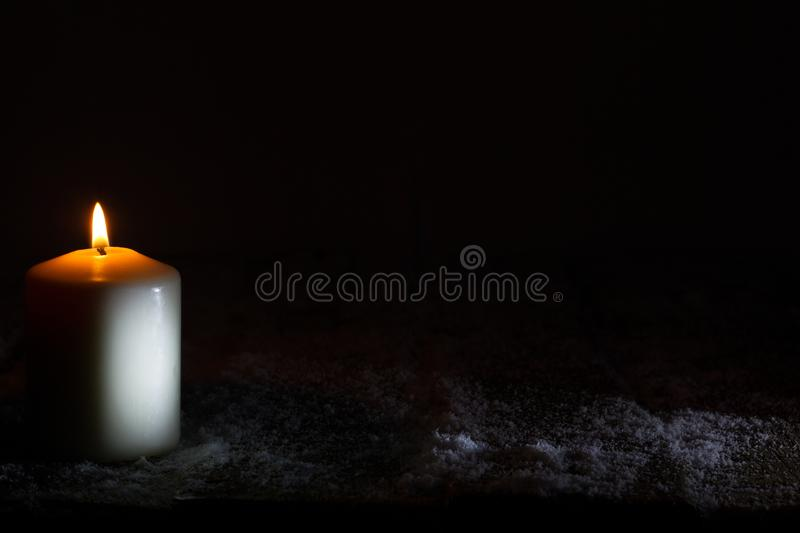 White candle in the night on wooden snowy board christmas abstract background with copy space. Closeup stock photography