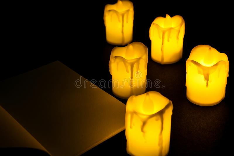 White candle and Notebook on black background isolated. Set of  candle.Small candle with light yellow spots on light background. Christmas decor royalty free stock image