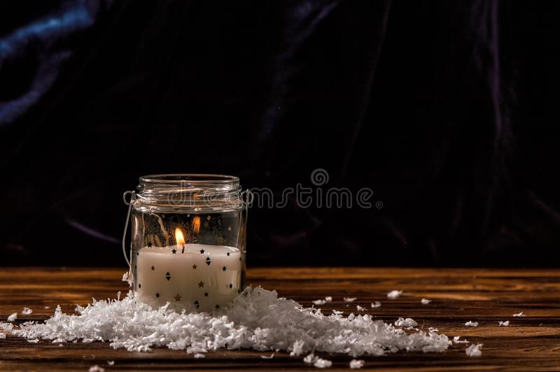 A white candle in a transparent glass jar is burning, artificial snow flakes are laid out around it. royalty free stock photo