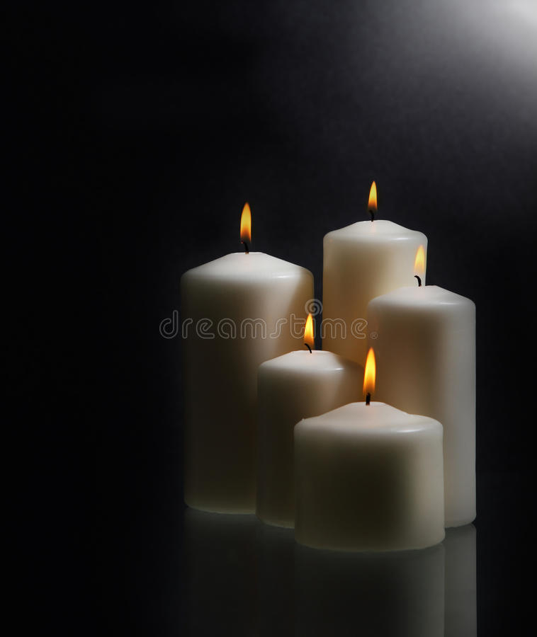 White candles over black background royalty free stock photos