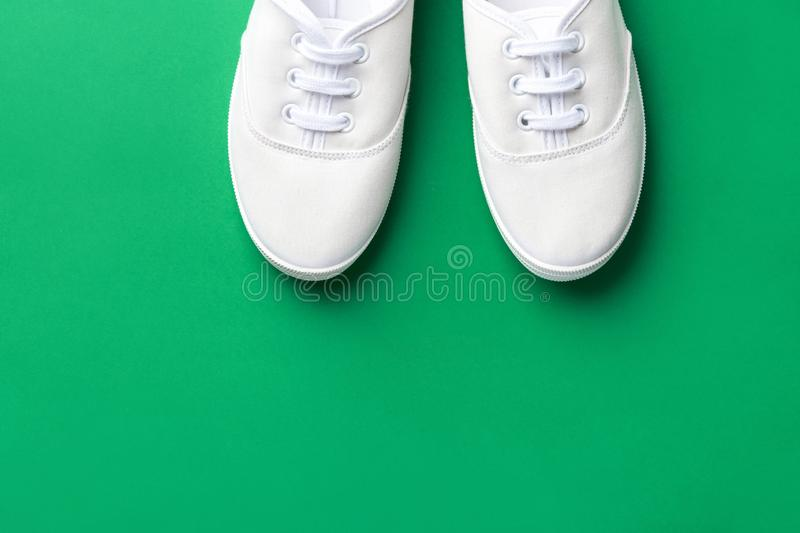 White canvas laced unisex shoes on green background. Classic casual sport footwear youth teenager urban fashion active lifestyle stock image