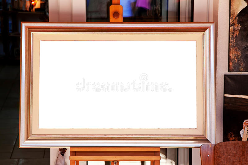 White canvas of picture frame on easel. White canvas in a gilded wooden frame on an easel in interior closeup stock photos