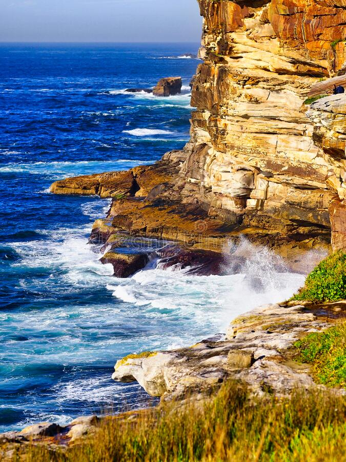 Pacific Ocean Waves Crashing at Bottom of Sandstone Cliffs, Sydney, Australia. White capped swirling pacific Ocean waves crashing at the bottom of high sandstone royalty free stock images