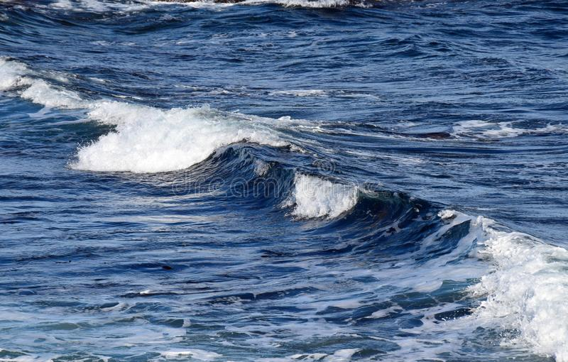 White capped waves on the blue ocean surface royalty free stock photography