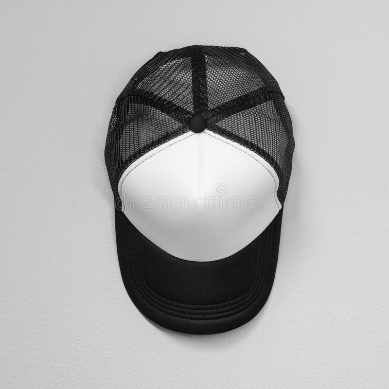White caps with black nets on cement background. Top view angle of baseball cap. Cap royalty free stock image