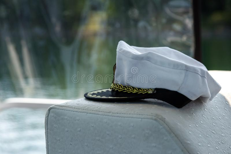 White captain hat near the steering wheel in a boat. Summer time vacation with sailboat in an open waters, captain hat in a yacht royalty free stock image
