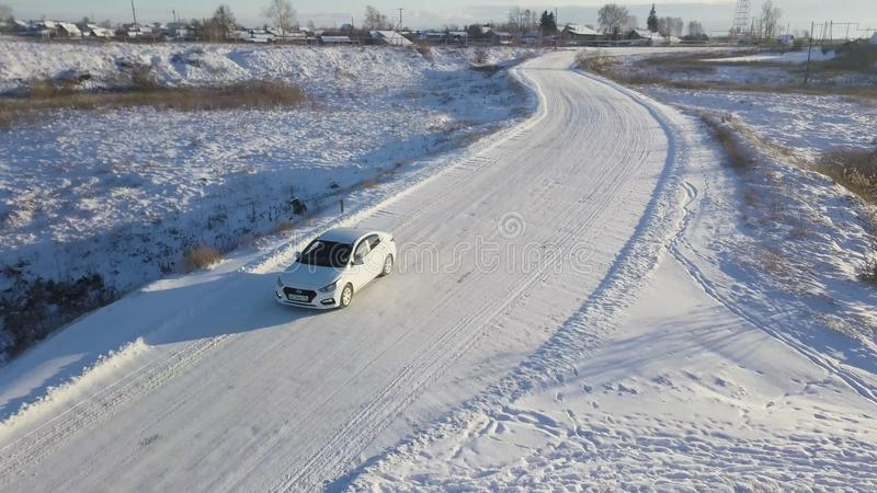 White car crossing the bridge covered with snow in the winter field with a narrow frozen river under it. Stock footage royalty free stock photography
