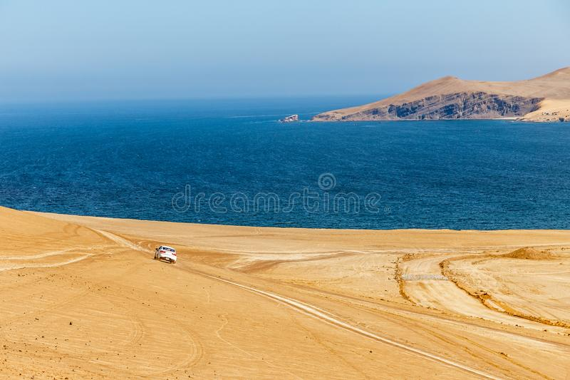 White car driving through Paracas desert toward the blue waters stock image
