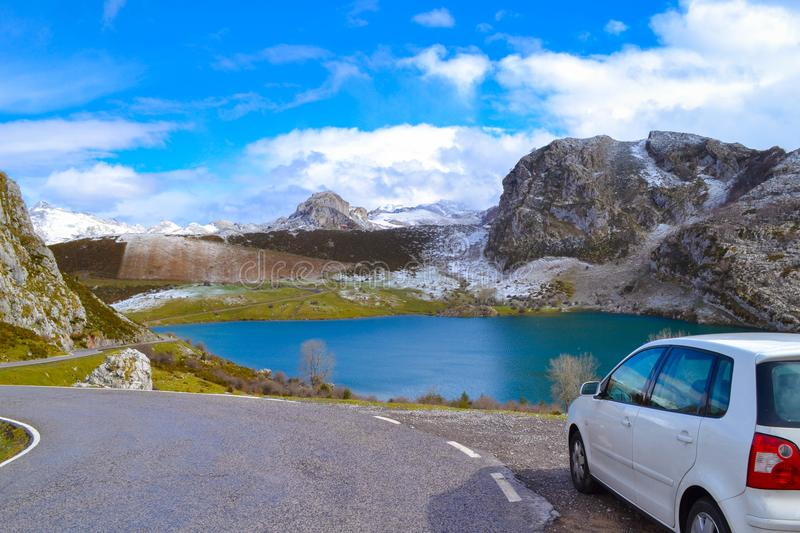 White car in Enol Lake in Picos de Europa, Asturias, Spain. Beau. Tiful view of a blue and clear lake in middle of mountains, with a car and road at the front royalty free stock images