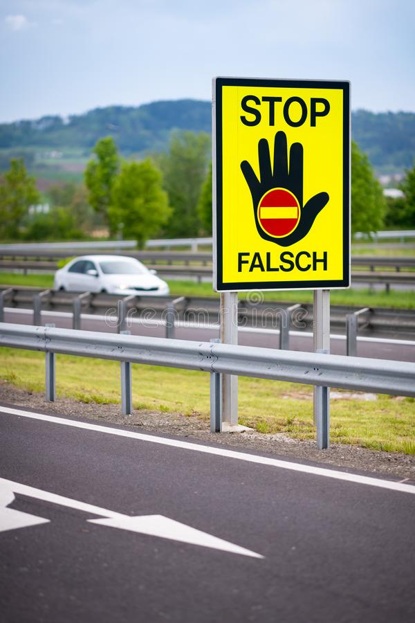 White car on the highway in the austrian countryside with the STOP/ FALSCH stop / false sign to warn the drivers royalty free stock photography