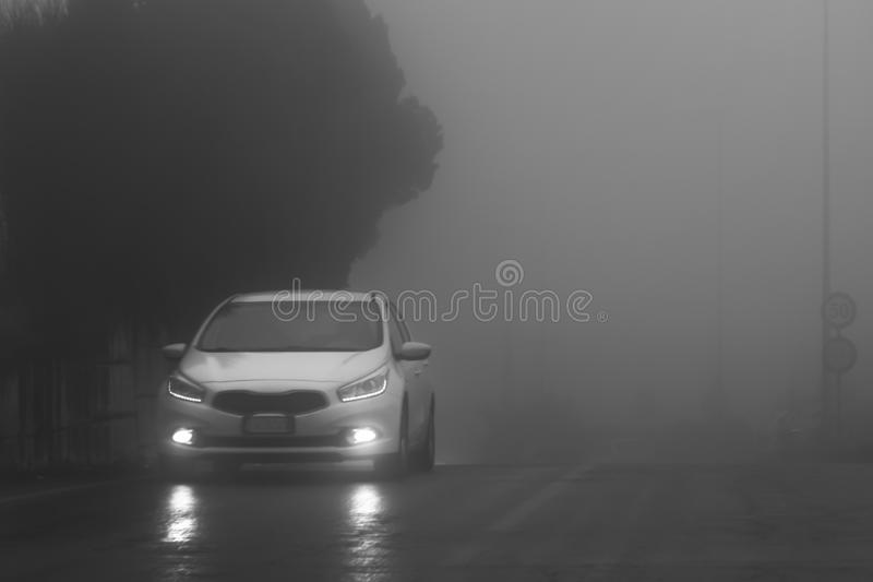 A white car with white lights on the wet road in the fog. Black and white photo. A white car with white lights is on the wet road in the fog. Black and white stock photo