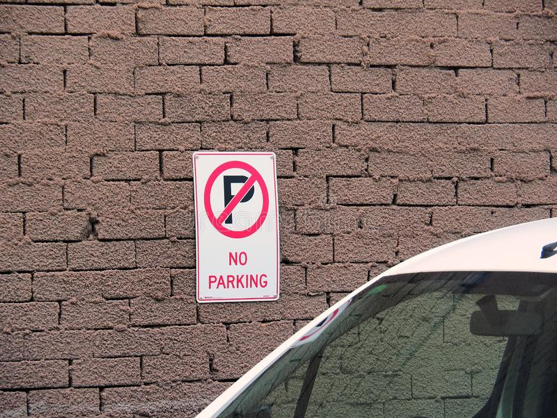 Car parked Near No parking Sign. A white car parked directly in front of a no parking sign. Flagrant disobedience, traffic offence royalty free stock photos
