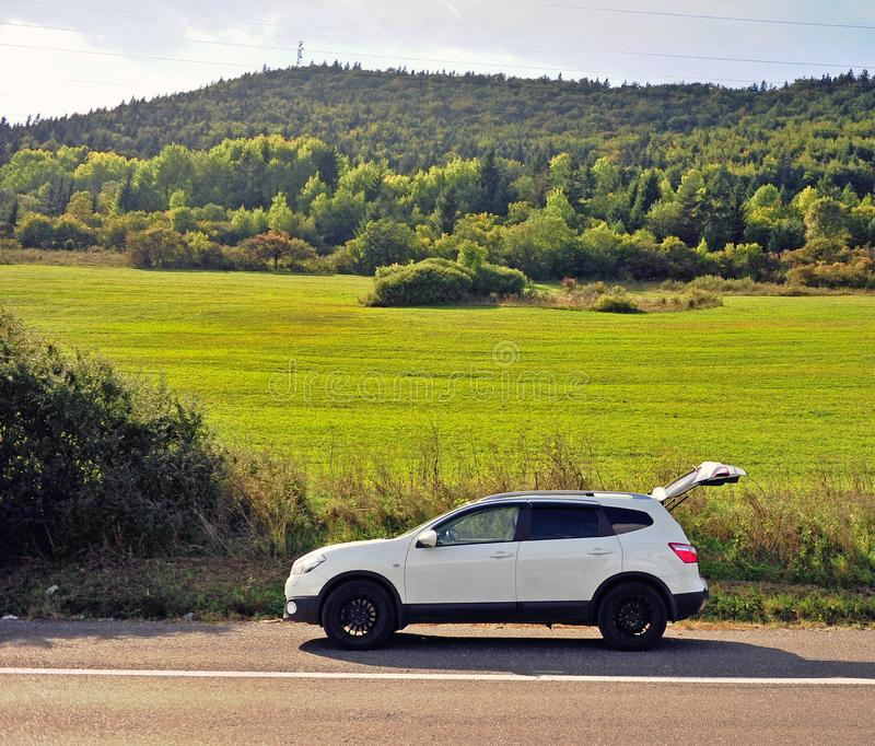 White car parked on the road. With green grass field on background royalty free stock photography
