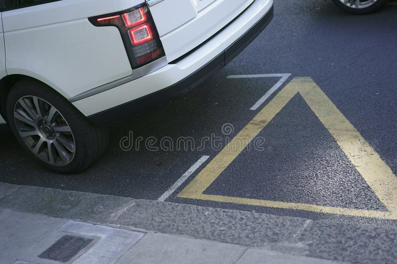 The white car parked. Near the sidewalk. Wheel and asphalt are visible stock images