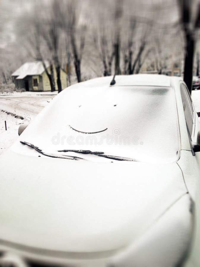 White car in snow with drawing smiley face on window. Happy and funny winter background. Snowy smile on car glass. stock photos
