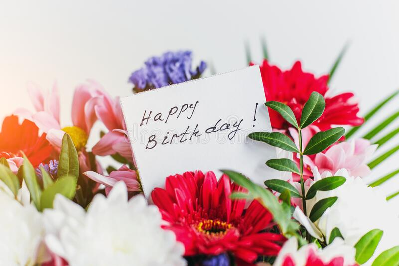 Card for a bouquet with the inscription happy birthday in a beautiful bouquet of flowers. White card for a bouquet with the inscription happy birthday in a royalty free stock images