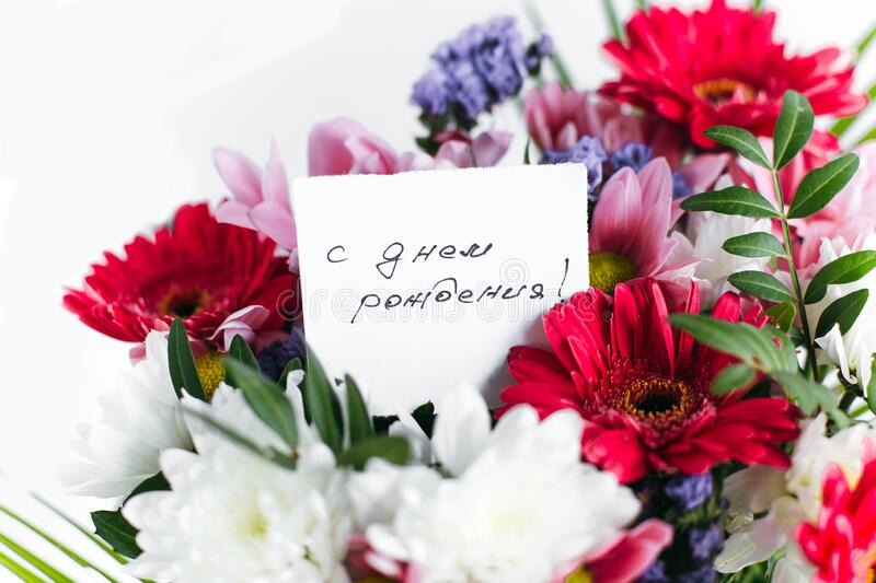 Card for a bouquet with the inscription happy birthday in russian in a bright beautiful bouquet of flowers. White card for a bouquet with the inscription happy royalty free stock image
