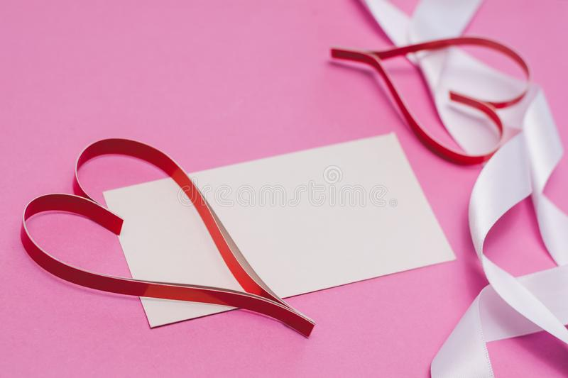 White card with with copy space, red homemade paper hearts and a white ribbon on a pink background. Symbol of Valentine`s Day royalty free stock images