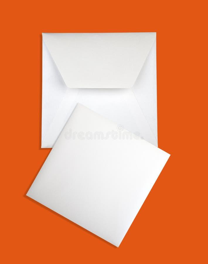 White card and envelope on orange background royalty free stock photo