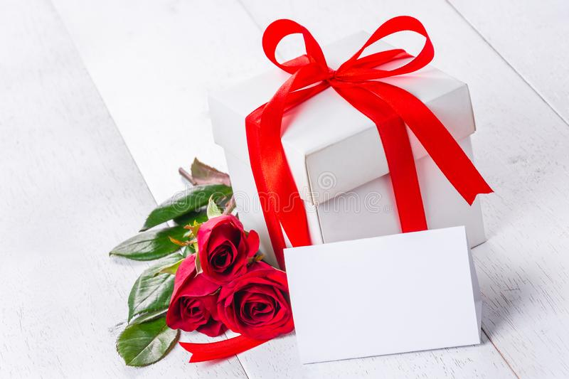 White card, gift box and roses on table. White gift box tied with red ribbon and roses on wooden table, blank card for text royalty free stock photography