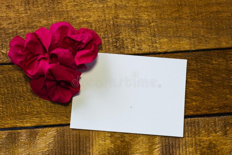 White card on wooden background with paper flower. blank for inscription stock images