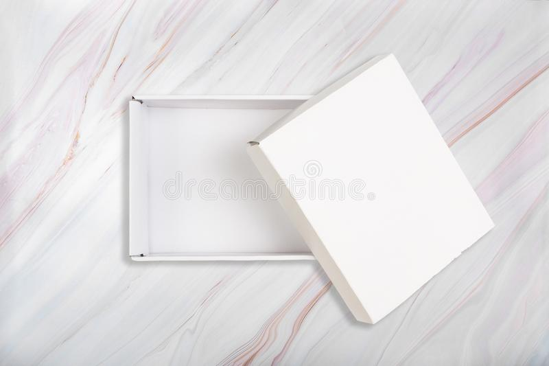 White cardboard box with open lid on natural marble pattern background. Open white box on marble texture. royalty free stock photos