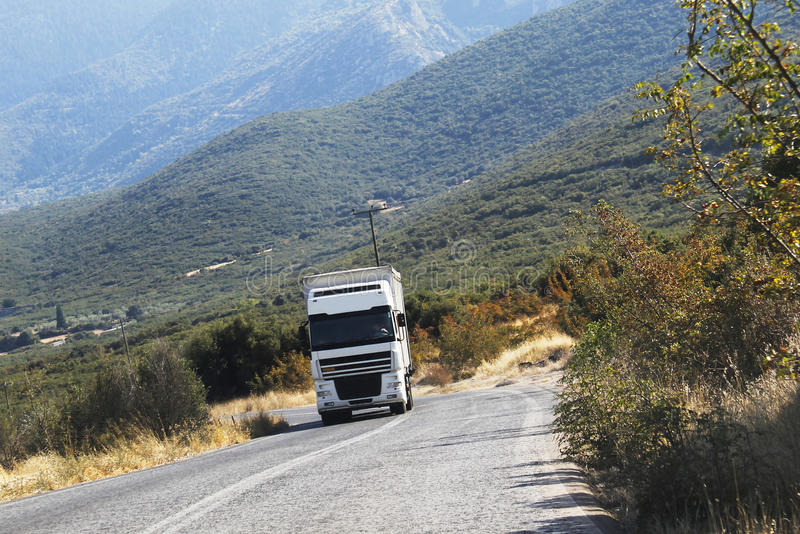 White cargo truck driving on mountain road royalty free stock photo