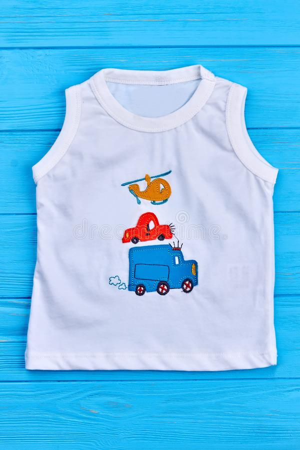 White cartoon baby boy t-shirt. Natural cotton toddler boy white t-shirt with cars and helicopter print on blue wooden background, vertical image stock photo