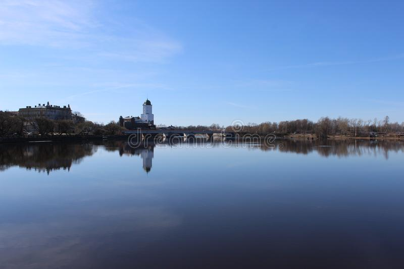 White castle with brick wall against blue sky, reflection in water. northern Europe stock images