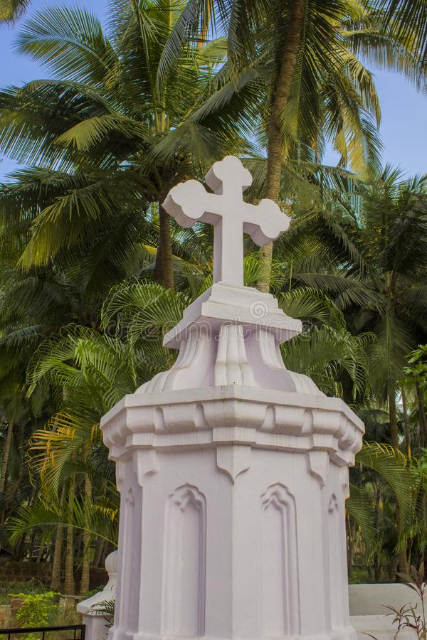White Catholic cross on the background of fresh bright green palm trees under a clear blue sky royalty free stock images