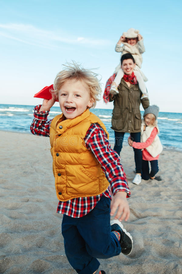 White Caucasian family, mother with three children kids playing paper planes, running on ocean sea beach on sunset outdoors royalty free stock photo