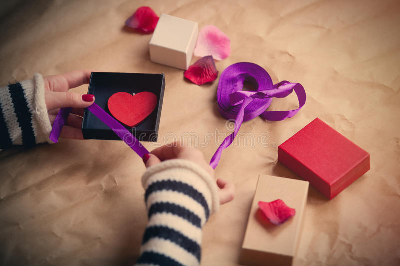 White caucasian hands wrapping heart shaped toy in box on the wonderful things for decoration background stock photo