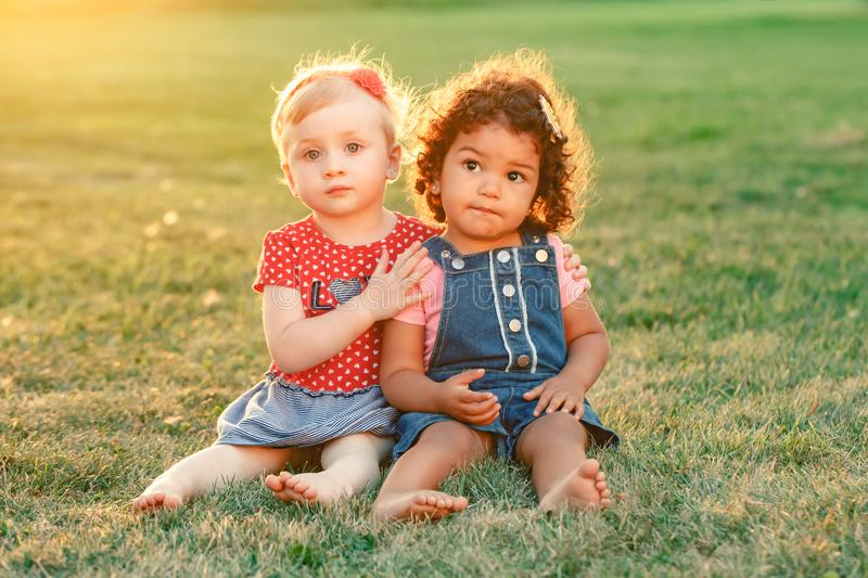White Caucasian and latin hispanic babies hugging outside in park. royalty free stock image
