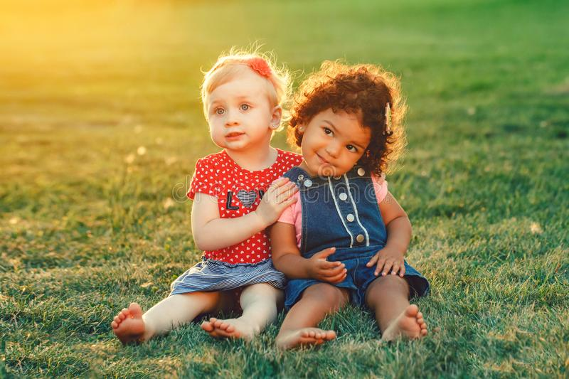 White Caucasian and latin hispanic babies hugging outside in park. stock images
