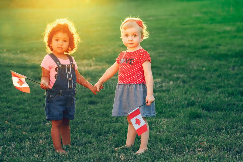 White Caucasian and latin hispanic babies hugging outside in park. royalty free stock photos
