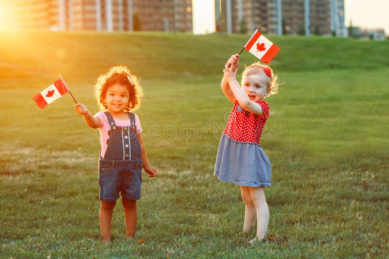 White Caucasian and latin hispanic babies hugging outside in park. royalty free stock images
