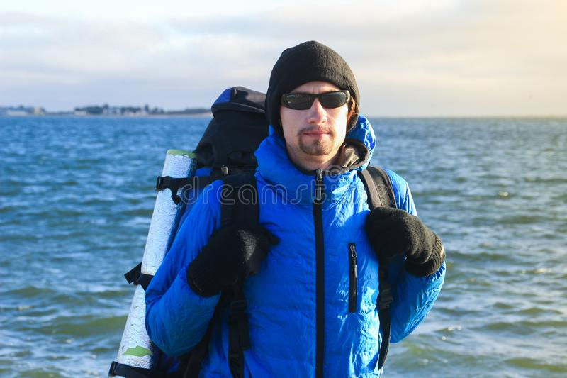 White Caucasian male traveler in a sports blue jacket, gloves, hat, glasses and a backpack stands against the background stock image