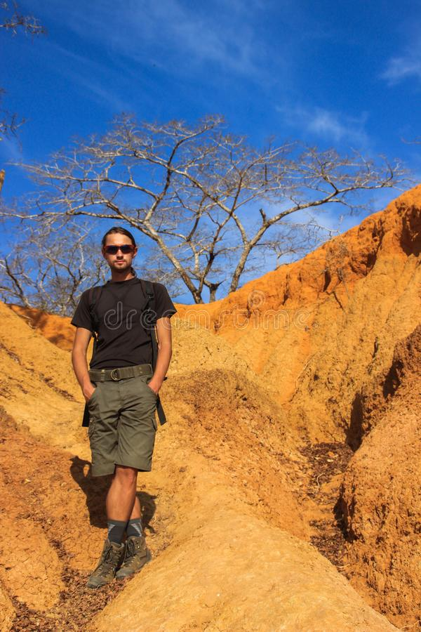 White Caucasian male traveler in sportswear: boots, shorts, wearing glasses stands against the bright yellow rocks in Kenya royalty free stock image