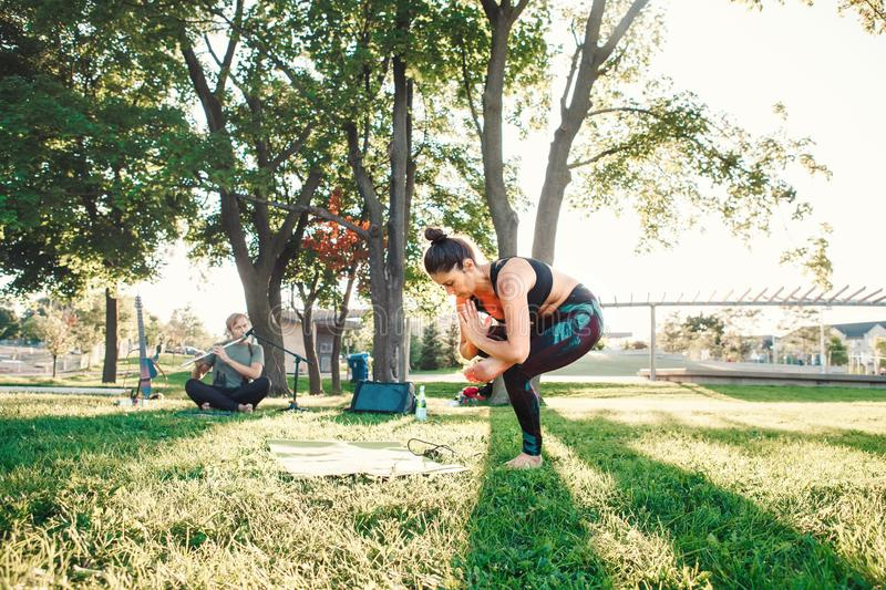 Middle age woman doing yoga in park outside on sunset stock photo