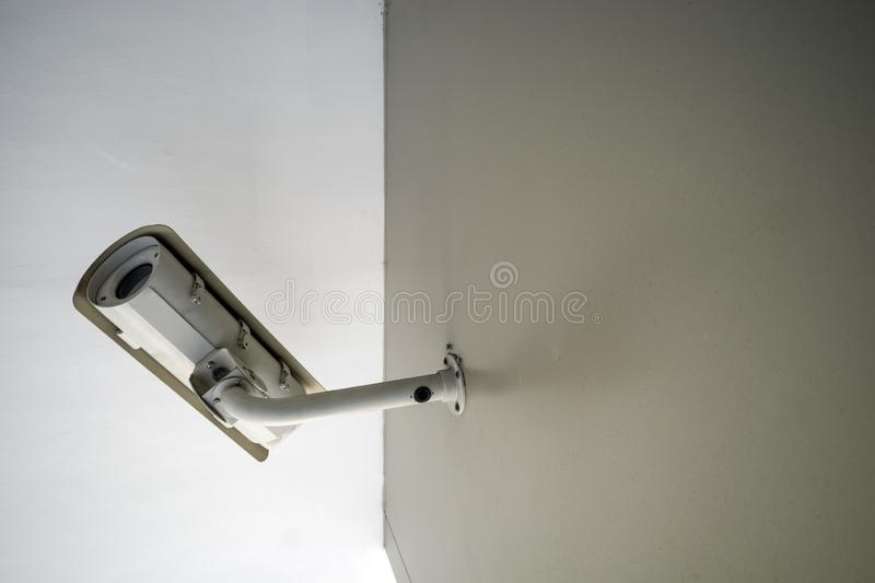 A white CCTV camera on brown wall stock image