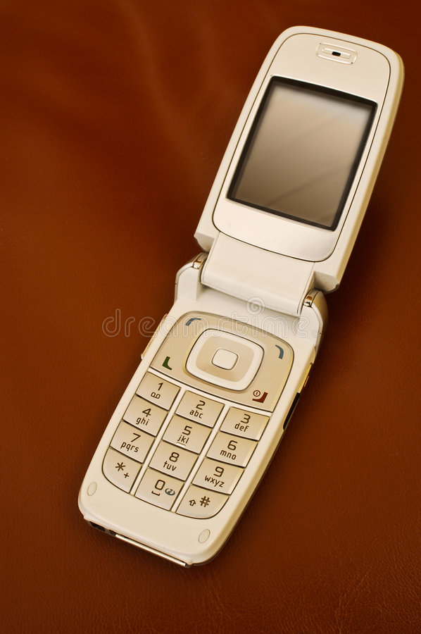 Open Flip Style Mobile Phone. Open silver flip phone on brown leather background royalty free stock image