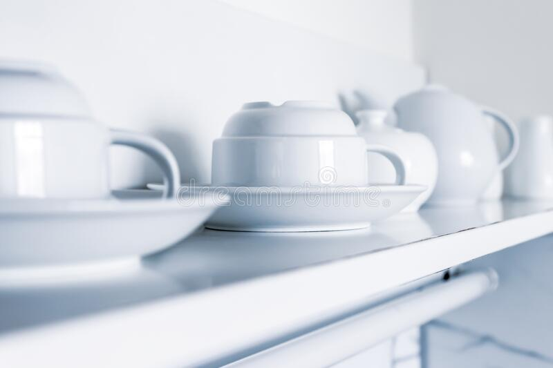 White ceramic coffee cups and saucers standing in a row on a shelf in kitchen stock images