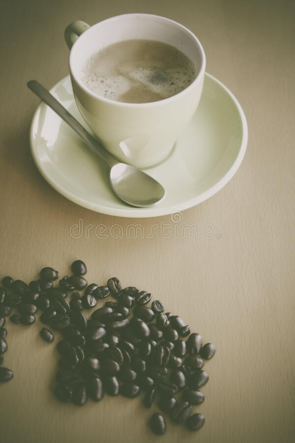 White Ceramic Coffee Mug Beside Silver Teaspoon on White Ceramic Plate stock photo