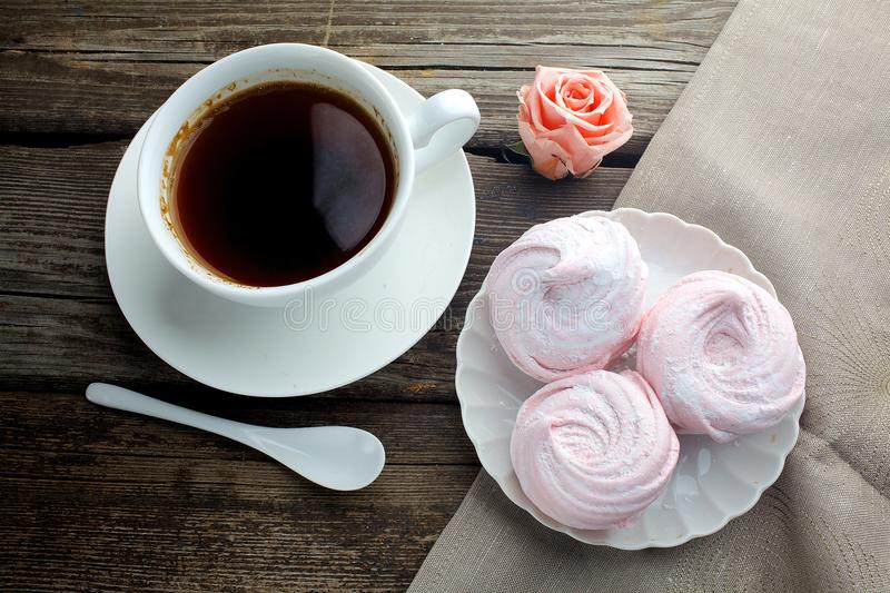 White ceramic cup with black coffee and marshmallow dessert on wooden table, top view stock image