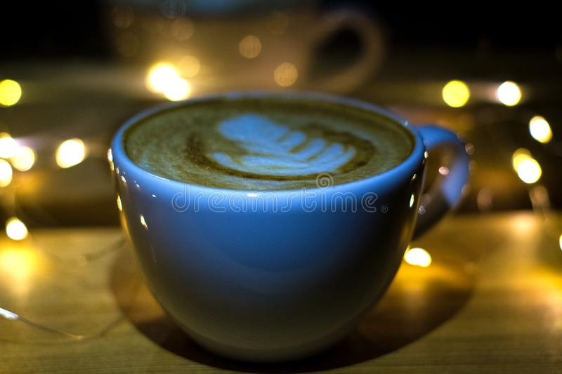 A white ceramic cup of cappuccino with latte art amid yellow flashlights in a dark coffee shop. Garland. Holiday. A white ceramic cup of cappuccino with latte royalty free stock photography