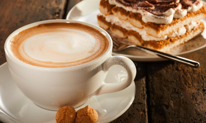 White ceramic cup of coffee with dessert. Cake, served on old wooden table surface, viewed in close-up from high angle stock images