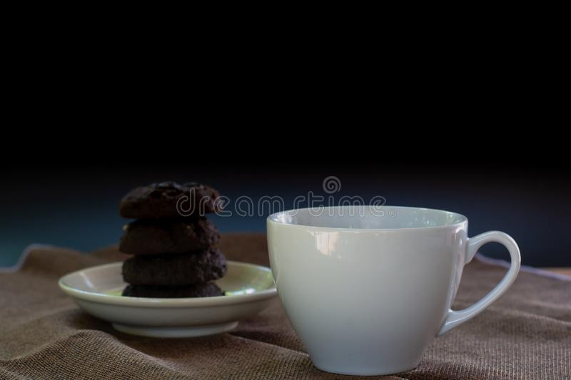 White ceramic cup of coffee serve with blurry dark chocolate cookies on black background stock photo