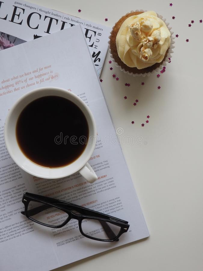 White Ceramic Cup With Coffee on Top of Opened Book and Near Eyeglasses stock image