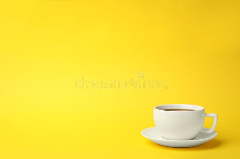 White ceramic cup with hot aromatic coffe. E on color background royalty free stock images