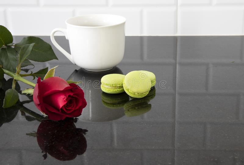White ceramic cup with macarons and a red rose royalty free stock photos